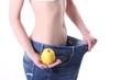 Junge Frau in zu großer Hose mit Apfel