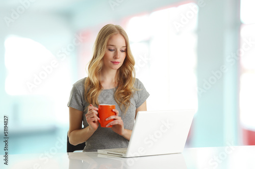 Young woman browsing on laptop and drinking coffee