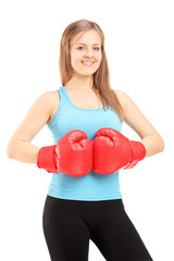 Young smiling female athlete wearing red boxing gloves and posin