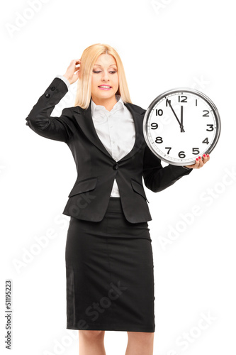 A young businesswoman holding a wall clock in her hand and gestu