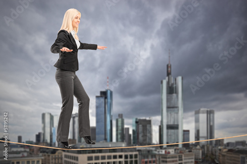 Businesswoman walking on a rope, with Frankfurt in the backgroun