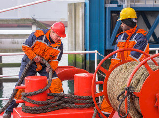 European deck officer working with ropes together with African s