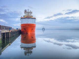 Orange supply vessel in a port with oil rig