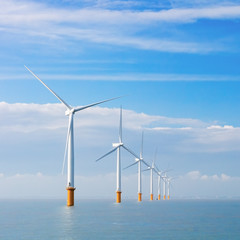wind power generators farm at sea with white clouds and blue sky