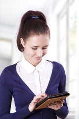 Student girl reading electronic books on an e-reader