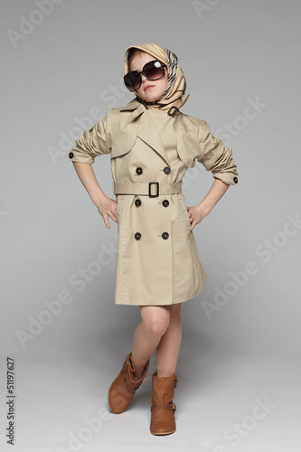 Little girl wearing trench coat and sunglasses