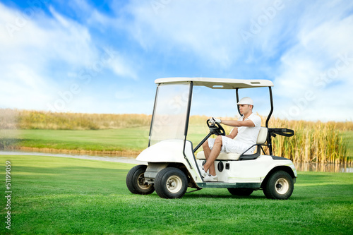 Young man driving golf buggy