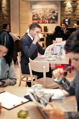 Young businessman sitting at table in cafe