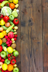 Fresh fruits and vegetables on the old wooden board