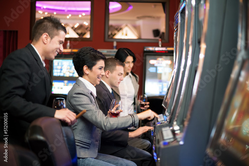 young people gambling in the casino on slot machines