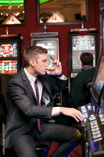 handsome man playing the slot machine