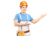 A manual worker with tool belt and helmet gesturing