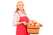 A woman with apron holding a bucket full of apples