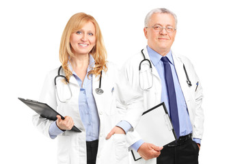 A team of doctors holding a clipboard and posing
