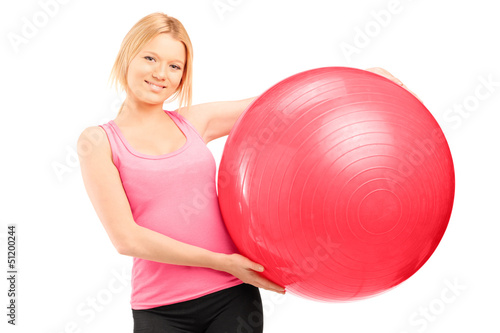 A blond female athlete holding a pilates ball