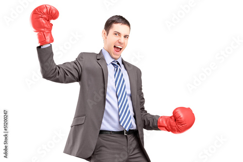 A businessman wearing red boxing gloves and gesturing happiness