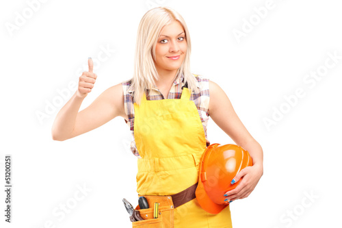 A female construction worker with equipment giving thumb up