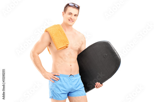 A hadsome man in a swimming suit holding a surfing board