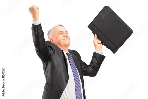 A happy mature businessman with raised hands
