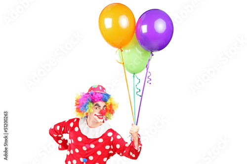 A male clown in costume holding bunch of balloons