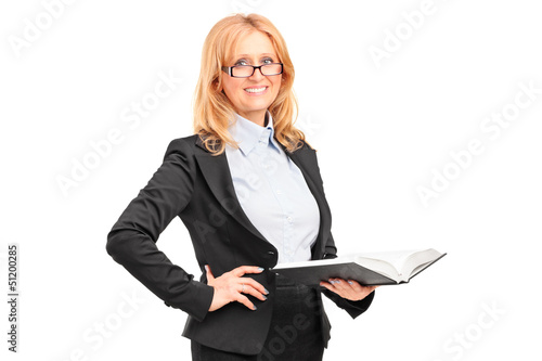 A smiling female teacher holding a notebook