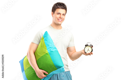 A smiling man in pajamas holding a pillow and alarm clock