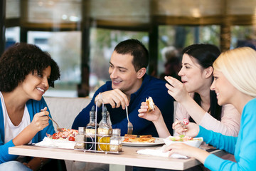 Cheerful friends chatting while lunch