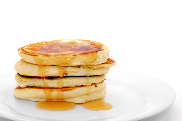 Stack of breakfast pancakes on plate with syrup