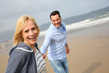 Cheerful woman running with husband on the beach