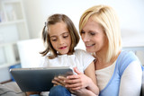 Mother and daughter playing with electronic tablet