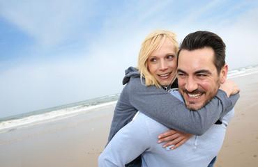 Middle-aged couple having fun on a sandy beach
