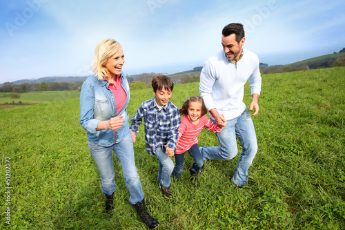 Family of four running together in natural landscape