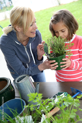 Mother and daughter in garden planting aromatic flowers
