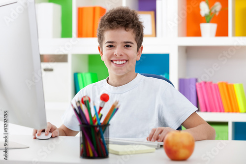cute boy using a computer and smiling