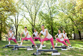 Fitness group in park stretching