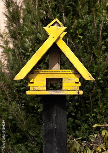 Gelbes Vogelhäuschen aus Holz auf einem Pfahl