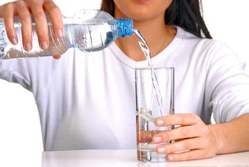 Mujer sirviendo agua potable en un vaso,agua mineral.