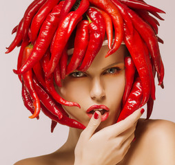 Hot Chili Pepper on Shiny Woman's Face. Creative Concept