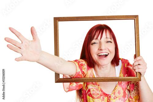 Lachende Frau streckt Arm durch Rahmen