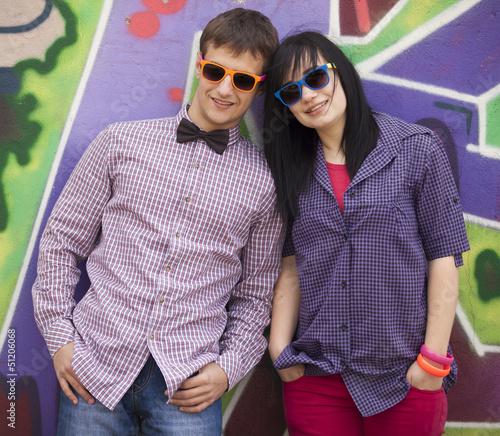 Style teen couple near graffiti background.