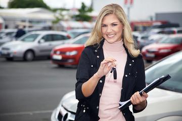 Hübsche Autoverkäuferin mit Schlüssel lächelt
