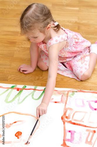 Pretty little girl painting sitting on the floor
