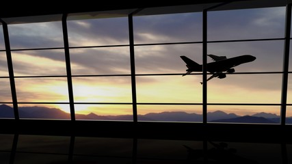 Airport window with airplane flying at sunset