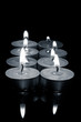 row of candles, in black and white photograph.