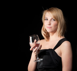 woman in black dress  with glass over dark background