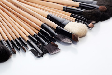 Collection of make-up brushes on white background