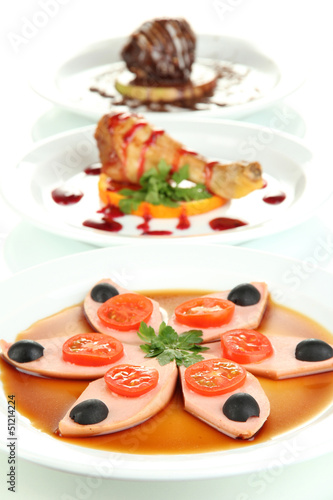 Small portions of food on big white plates isolated on white