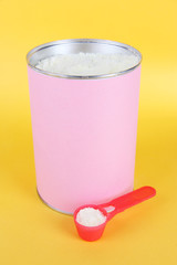 Powdered milk for baby on yellow background