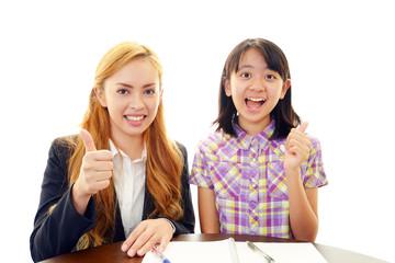ガッツポーズをして喜ぶ女性教師と女の子