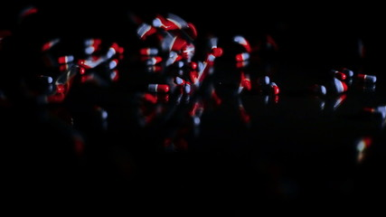 Pills capsules falling onto black glass